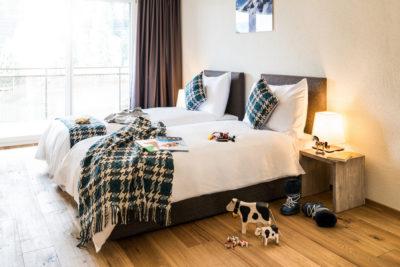 Schlafzimmer mit zwei Einzelbetten für Kinder im Apartment Hotel Peaks Place in Laax
