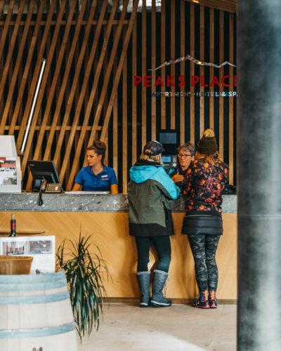 Mitarbeiterinnen und Gäste an der Rezeption vom Peaks Place Hotel in Laax