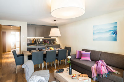 living area with sofa, table and kitchenette at peaks place aparthotel switzerland