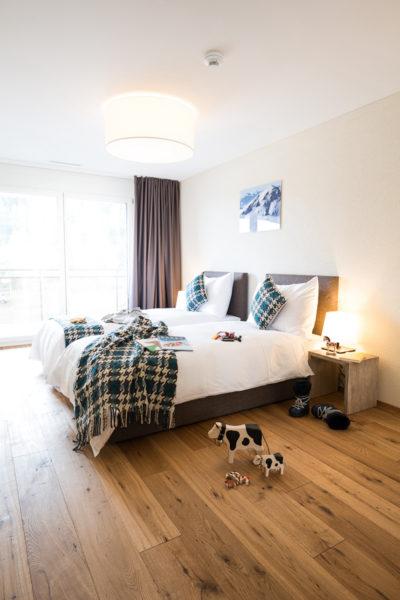 Schlafzimmer mit zwei Einzelbetten im Apartment im Peaks Place, Ferienwohnung in Laax mieten