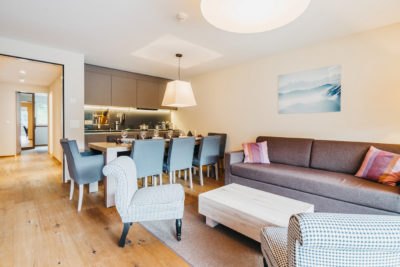 Wohnzimmer mit Esstisch für acht Personen in der Ferienwohnung in Laax im Aparthotel Peaks Place