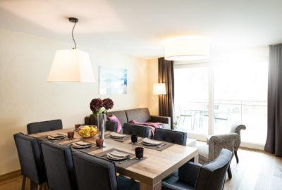 Wohnzimmer mit Esstisch in der Ferienwohnung in Laax im Aparthotel Peaks Place