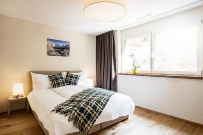 Doppelbett in der Ferienwohnung in Laax im Apartment Hotel Peaks Place