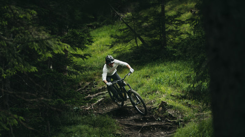 person fährt downhill mountain bike in dunklem wald in alpen laax