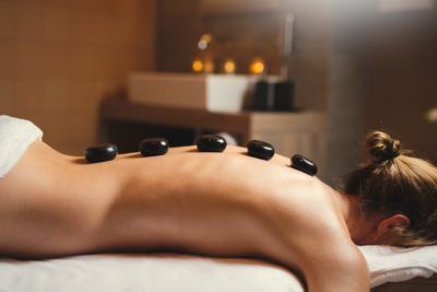 woman getting hot stone massage in la senda spa and wellness at peaks place laax