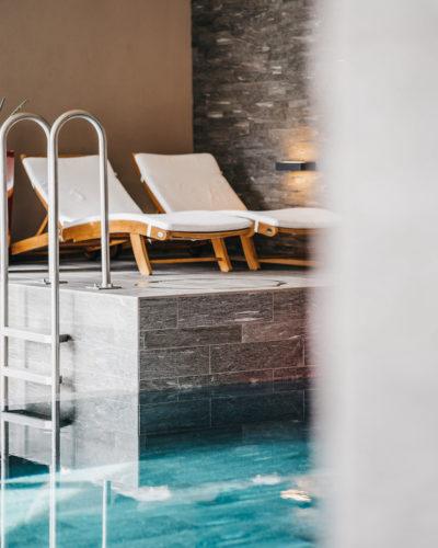 Ruheliegen am Schwimmbecken im Peaks Place, Wellnesshotel Flims Laax