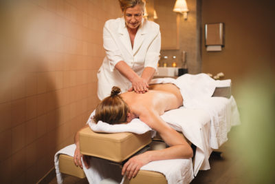 masseuse giving woman massage in la senda wellness and day spa at peaks place laax