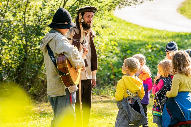 family package sardona men playing guitar for children in summer tour at family hotel peaks place
