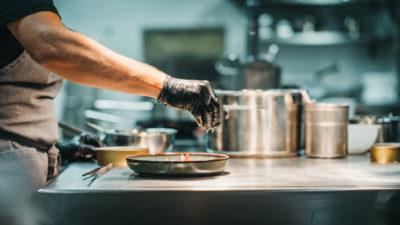 Koch dekoriert Teller in der Küche im Restaurant snani in Laax im Peaks Place