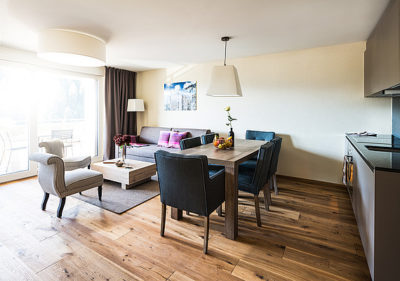 living area with sofa table and kitchenette in rent 2.5 room apartment at peaks place laax